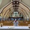 Un curé donne une messe dans une église où les fidèles sont assis à une bonne distance l'un de l'autre.
