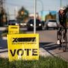 Un homme en vélo passe devant une affiche jaune d'Élections Canada plantée dans une pelouse.