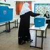 Une femme portant le voile dépose son bulletin de vote dans l'urne, sous le regard d'un observateur.