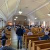Les citoyens assis dans l'église assistent à une rencontre avec les candidats aux élections municipales.