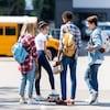Des élèves du secondaire devant un autobus scolaire dans une cour d'école.