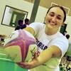Elizabeth Gaspo qui tient un ballon de rugby dans un gymnase où se trouvent des enfants.