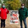Ellen Gabriel et Al Harrington portent le masque et tiennent une affiche. Ils se trouvent dans la pinède entre Oka et Kanesatake.