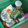 Une boîte verte contenant divers emballages recyclables.