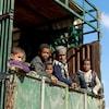 Des garçons assis dans la boîte d'un camion.