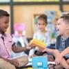 Dans une garderie, deux jeunes garçons rient en échangeant un jouet. Derrière eux, une fillette les observe.