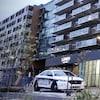 Deux voitures de la police stationnés au pied d'une barre d'immeubles.