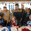 Trois personnes, assises à une table, signent l'entente. Plusieurs autres personnes se tiennent debout derrière elles.