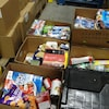 Des boîtes de céréales, de croustilles et de papiers mouchoirs sont dans des boîtes de carton posées au sol.