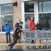 Des personnes masquées font la file à l'extérieur de l'épicerie.
