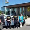 Des gens posent devant un poste de police.
