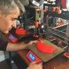 Un homme imprime des masques à l'aide d'une imprimante 3D.