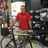 Éric Villeneuve pose devant un vélo dans un magasin de sport.
