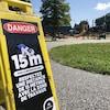Un panneau dans un parc demandant de respecter une distance de 15 mètres pour des questions de sécurité.