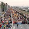 Un long cortège de manifestants s'étend jusqu'au loin. Des drapeaux catalans jaune et rouge flottent au vent.
