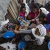 Une dizaine de personnes s'entasse près de l'entrée d'un local où de la nourriture leur est donnée.