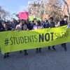 Des étudiants marchent en rangs. Le premier rang tient une large banderole. Il y est écrit en anglais les étudiants ne seront pas silencieux.