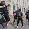 Des étudiants portant des sacs à dos marchent dans un campus universitaire.