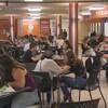 Des étudiants discutent assis à des tables.