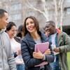 Cinq étudiants internationaux discutent et rient en marchant sur un campus universitaire.