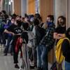 Des étudiants masqués forment une file d'attente dans les couloirs de l'université.