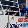 Des gens versent une bouteille de champagne sur le nom d'un bateau.