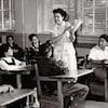 Une femme tient un livre debout au milieu d'une classe composée d'élèves autochtones.