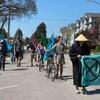 Sept personnes défilent à pied et à vélo dans une rue résidentielle sous un ciel bleu lors d'une journée ensoleillée.