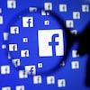 Plusieurs logos de Facebook sur un écran, vus à travers une loupe.