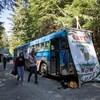 Des militants devant un autobus arrêté le long d'un chemin forestier, avec des affiches sur lesquelles sont inscrits des slogans pour la protection des forêts anciennes.