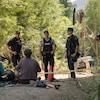 Trois policiers debout devant deux manifestants assis au sol.