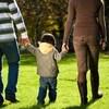 Un homme et une femme tiennent chacun la main d'en enfant, en marchant, dos à la caméra.
