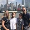 Une femme et un homme avec leurs deux enfants devant la ville de Shanghai.