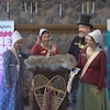 La famille de voyageurs, dans leurs costumes traditionnels, souriants, devant une estrade. En arrière, des bannières indiquent « Hé Ho, 50 ans ».
