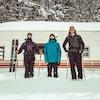 Trois jeunes hommes en tenue de ski sourient devant leur caravane