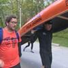 Félix Jasmin marche avec un coéquipier en portant son canot.