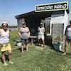 Quatre femmes posent devant un cabanon avec une affiche Ferme Esther Aubin.