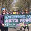 Deux participants ouvrent le défilé avec une banderole sur lequel est écrit le nom du festival.