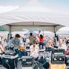 Un groupe de musique sur une scène sur la plage. Quelque centaines de festivalier les écoutent