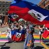Personnes agitant des drapeaux d'Haïti.