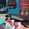 Deux cupcakes devant un comptoir mobile dans un stationnement.