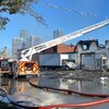 Un camion de pompier devant la boulangerie au toit effondré et aux murs noircis par le feu.