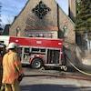 Trois pompiers et un camion de pompier devant l'église Saint-Joachim à Chicoutimi.