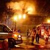 Vue d'ensemble de la scène : ambulance, camion de pompiers, pompiers, flammes qui sortent par les fenêtres de l'immeuble.