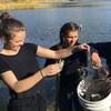 Trois adolescents déposent du fil à pêche dans un seau. Derrière eux, un lac.