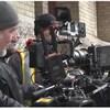 Un homme derrière une caméra et deux autres personnes à droite de la caméra.
