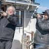 Un caméraman filme Raôul Duguay qui pointe au loin à bord d'un bateau.