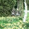 Deux religieuses assises sur un banc de parc, entourées de massifs de fleurs.