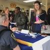 Un policier assis derrière une table sur laquelle se trouvent des prospectus de recrutement parle à une candidate potentielle.