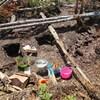 Des trous sont creusés dans la terre et des objets sont répartis dans de petits récipients.